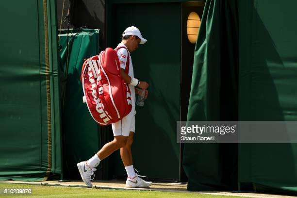 Kei Nishikori of Japan looks dejected in defeat after the Gentlemen's Singles third round match against Roberto Bautista Agut of Spain on day five of...
