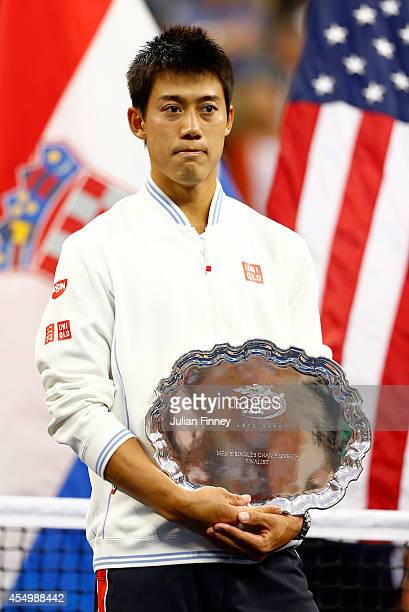 Kei Nishikori of Japan looks on with his runners up trophy after losing against Marin Cilic of Croatia in the men's singles final match on Day...