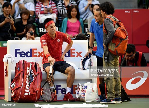 Kei Nishikori of Japan makes grimaces as he talks with a doctor and a trainer during the men's singles second round match against Joao Sousa of...