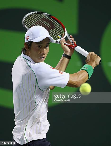 Kei Nishikori of Japan plays a backhand against Roger Federer of Switzerland during their quarter final round match during day 10 at the Sony Open at...