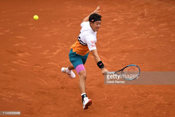 Kei Nishikori of Japan plays a backhand against Taylor Fritz of the United States in their round of 32 match during day two of the Barcelona Open...