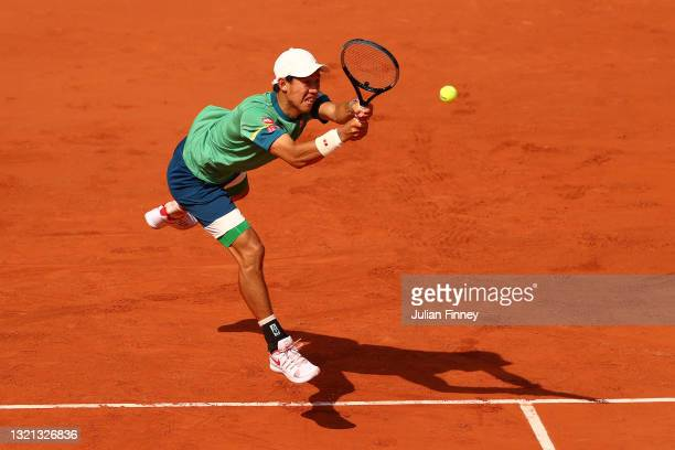 Kei Nishikori of Japan plays a backhand during his mens second round match against Karen Khachanov of Russia during day four of the 2021 French Open...