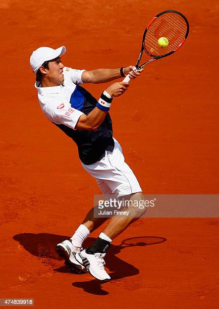 Kei Nishikori of Japan plays a backhand during his Men's Singles match against Thomaz Bellucci of Brazil during day four of the 2015 French Open at...