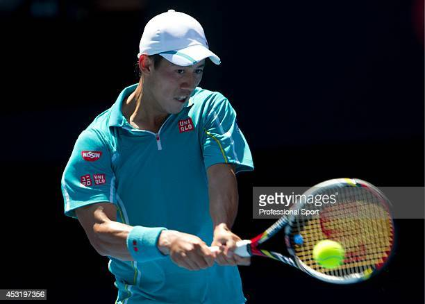 Kei Nishikori of Japan plays a backhand in his fourth round match against David Ferrer of of Spain during day seven of the 2013 Australian Open at...