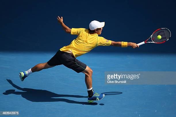 Kei Nishikori of Japan plays a backhand in his fourth round match against Rafael Nadal of Spain during day eight of the 2014 Australian Open at...