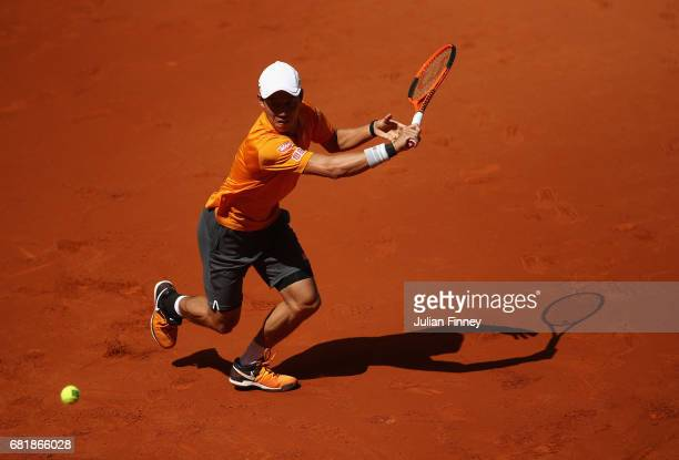 Kei Nishikori of Japan plays a backhand in his match against David Ferrer of Spain during day six of the Mutua Madrid Open tennis at La Caja Magica...