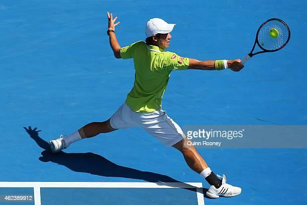 Kei Nishikori of Japan plays a backhand in his quarterfinal match against Stanislas Wawrinka of Switzerland during day 10 of the 2015 Australian Open...
