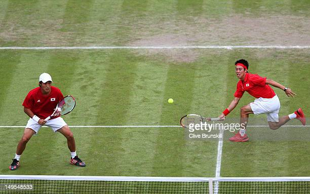 Kei Nishikori of Japan plays a forehand next to his partner Go Soeda of Japan during their Men's Doubles Tennis match against Stanislas Wawrinka and...