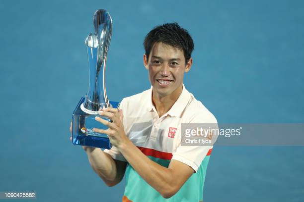 Kei Nishikori of Japan plays hold the winners trophy after thd Men's Finals match against Daniil Medvedev of Russia during day eight of the 2019...