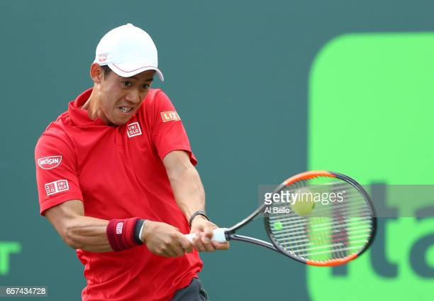Kei Nishikori of Japan returns a shot against Kevin Anderson of South Africa during day 5 of the Miami Open at Crandon Park Tennis Center on March 24...