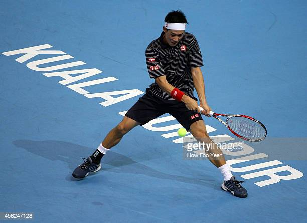 Kei Nishikori of Japan returns a shot to Julien Benneteau of France in the mens single finals during the Malaysian Open at Putra Stadium on September...