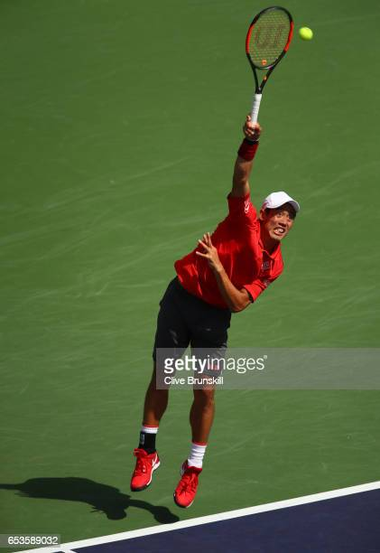 Kei Nishikori of Japan serves against Donald Young of the United States in their fourth round match during day ten of the BNP Paribas Open at Indian...