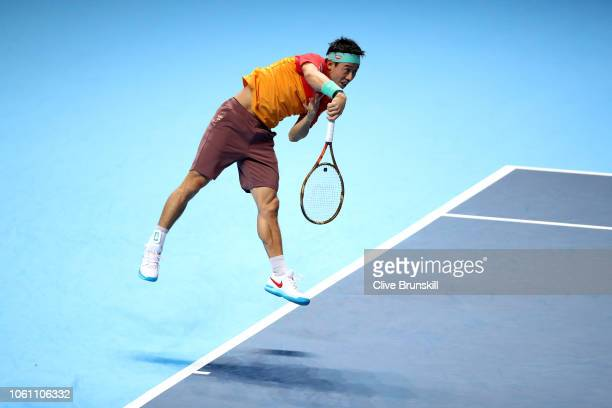 Kei Nishikori of Japan serves during his singles round robin match against Kevin Anderson of South Africa during Day Three of the Nitto ATP Finals at...
