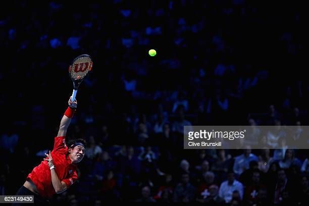 Kei Nishikori of Japan serves during the mens singles match against Stan Wawrinka of Switzerland on day two of the ATP World Tour Finals at at O2...