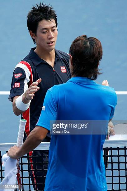Kei Nishikori of Japan shakes hands with Go Soeda of Japan after their first round match during day two of the Rakuten Open at Ariake Colosseum on...