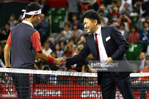 Kei Nishikori of Japan shakes hands with Hiroshi Mikitani chairman and chief executive officer of Rakuten Inc before the men's singles final match...