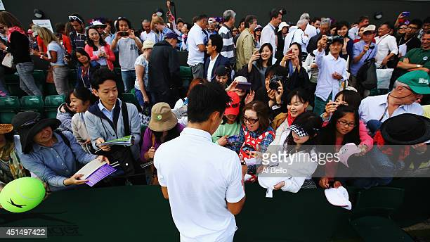 Kei Nishikori of Japan signs autographs for fans after winning his Gentlemen's Singles third round match against Simone Bolelli of Italy on day seven...