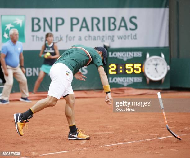 Kei Nishikori of Japan smashes his racquet in frustration after losing a point to Chung Hyeon of South Korea in the third round of the French Open in...