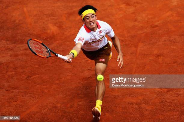 Kei Nishikori of Japan stretches and returns a forehand in his match against Grigor Dimitrov of Bulgaria during day 4 of the Internazionali BNL...