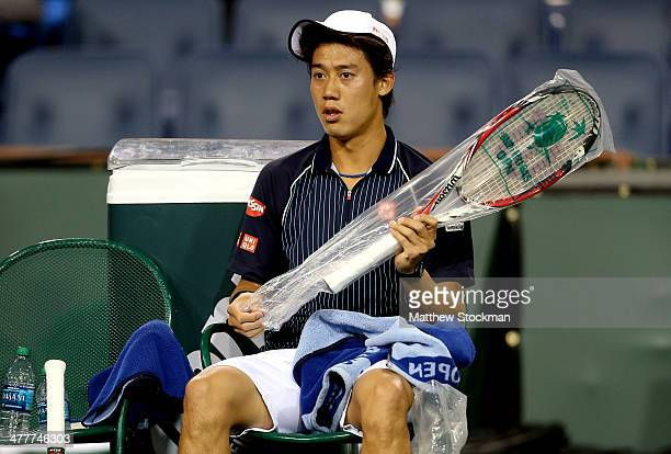 Kei Nishikori of Japan unwraps a new racquet between games while playing Tommy Haas of Germany during the BNP Parabas Open at the Indian Wells Tennis...