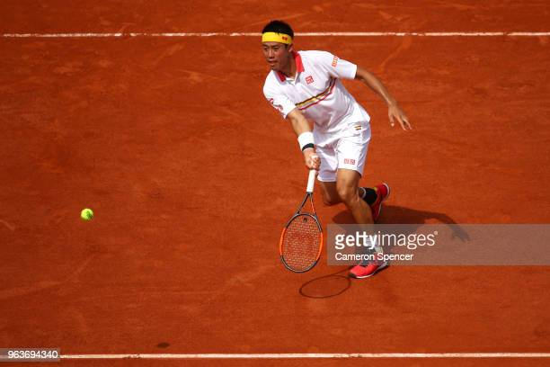 Kei Nishikori of Japan volleys during his mens singles second round match against Benoit Paire of France during day four of the 2018 French Open at...