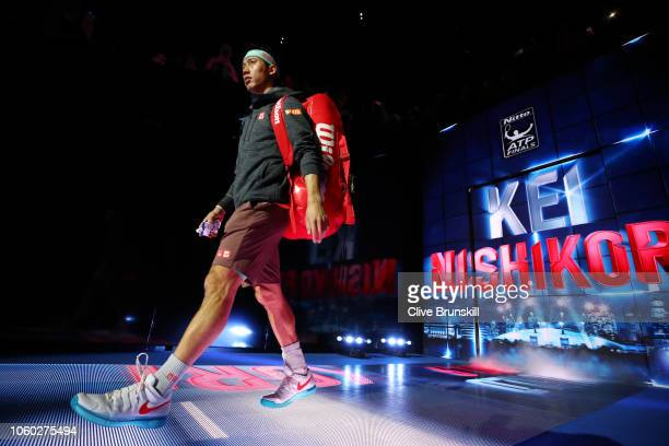Kei Nishikori of Japan walks onto the court ahead of his match against Roger Federer of Switzerland during Day One of the Nitto ATP Finals at The O2...