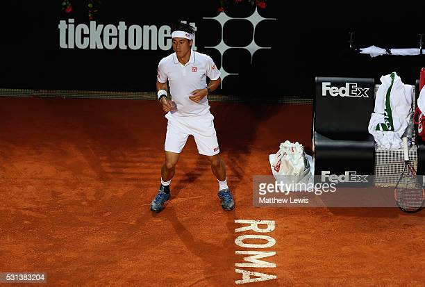 Kei Nishikori of Japan warms up whilst Novak Djokovic of Serbia has a medical time out during day seven of The Internazionali BNL d'Italia 2016 on...