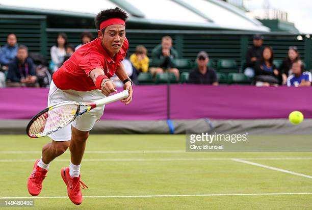 Kei Nishikori of Japan's racquet slips out of his hand as he stretches to return the ball during the Men's Singles Tennis match against Bernard Tomic...