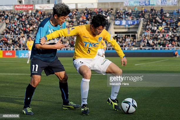 Kei Omoto of Tochigi SC and Kazuyoshi Miura of Yokohama FC compete for the ball during the J League 2nd division match between Yokohama FC and...