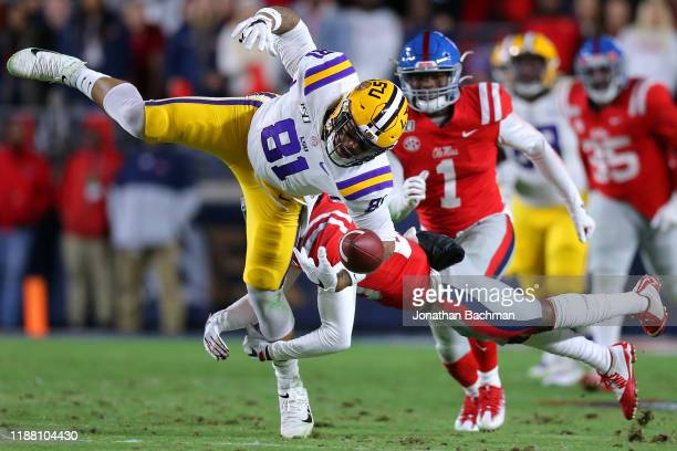 Keidron Smith of the Mississippi Rebels forces a fumble on Thaddeus Moss of the LSU Tigers during the first half of a game at VaughtHemingway Stadium...