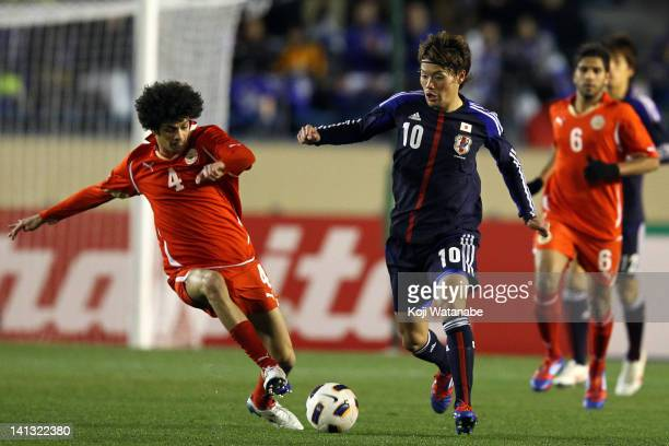 Keigo Higashi of Japan and Hassan Jameel Abdqaheri of Bahrain compete for the ball during the London Olympic after the London Olympic Menfs Soccer...