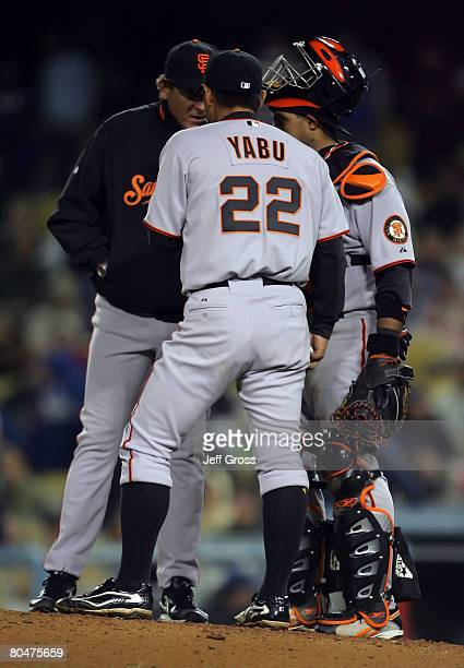 Keiichi Yabu of the San Francisco Giants talks with pitching coach Dave Righetti and catcher Bengie Molina during the game against the Los Angeles...