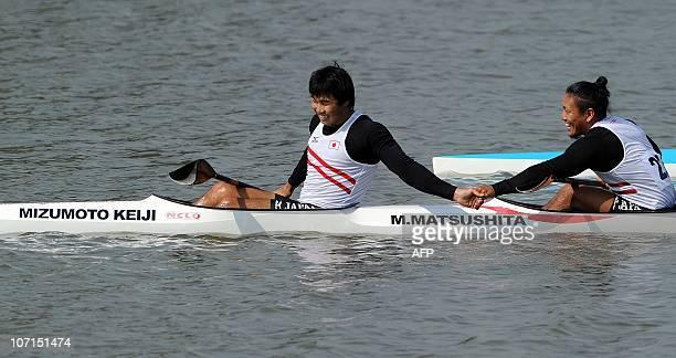 Keiji Mizumoto and Momotaro Matsushita of Japan celebrate winning the men's kayak double 200m final at the 16th Asian Games in Guangzhou on November...