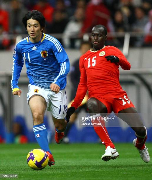 Keiji Tamada of Japan and Abdulla Omar of Bahrain compete for the ball during the 2010 FIFA World Cup Asian qualifier match between Japan and Bahrain...