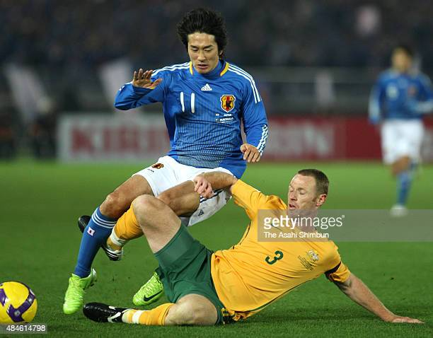Keiji Tamada of Japan is tackled by Craig Moore of Australia during the 2010 FIFA World Cup Aisan Qualifier match between Japan and Australia at...