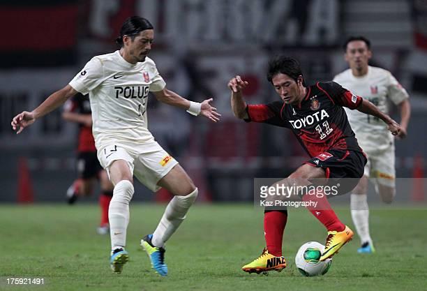 Keiji Tamada of Nagoya Grampus and Keita Suzuki of Urawa Red Diamonds compete for the ball during the J.League match between Nagoya Grampus and Urawa...