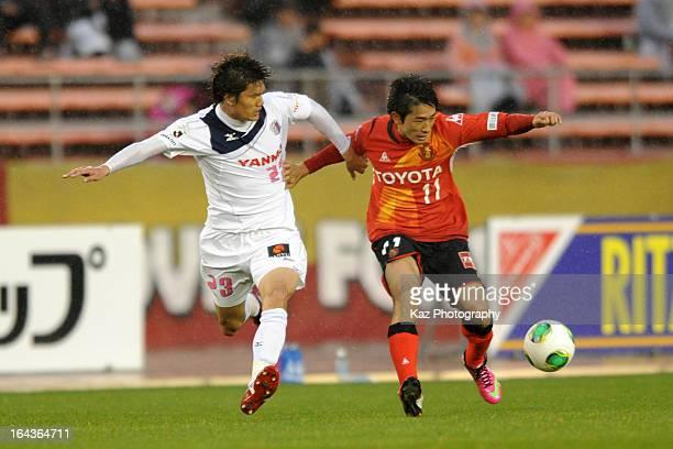 Keiji Tamada of Nagoya Grampus and Tatsuya Yamashita of Cerezo Osaka compete for the ball during the J.League Yamazaki Nabisco Cup match between...