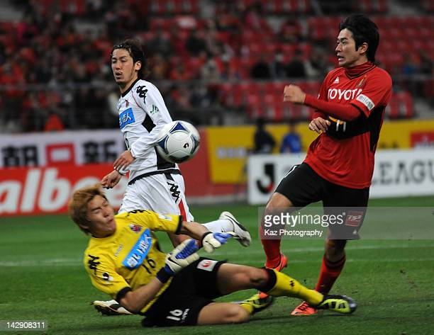 Keiji Tamada of Nagoya Grampus battles for the ball with Lee Ho Seung of Consadole Sapporo during the J.League match between Nagoya Grampus and...