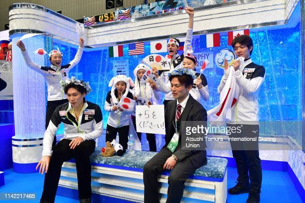 Keiji Tanaka of Japan waits for his score at the kiss and cry with his team mates after competing in the Men's Single Free Skating on day two of the...