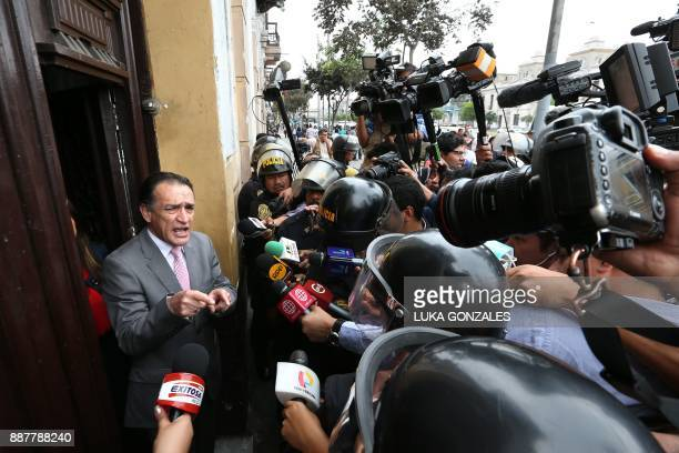 Keiko Fujimori's Fuerza Popular party congressman Hector Becerril talks to the press while police officers and prosecutor's office members search...