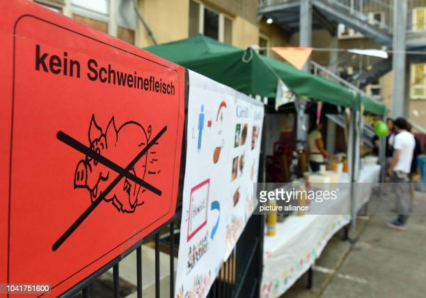 'Kein Schweinefleisch' is written on a sign during a summer party at the BBQ booth in the transitional refugee accomodation facility in...