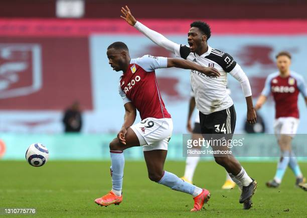 Keinan Davis of Aston Villa runs with the ball under pressure from Ola Aina of Fulham during the Premier League match between Aston Villa and Fulham...