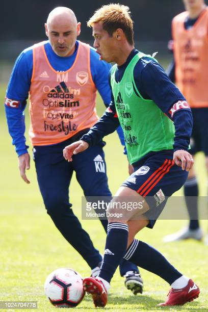 Keisuke Honda kicks the ball past Victory head coach Kevin Muscat during a Melbourne Victory training session at Gosch's Paddock on August 28 2018 in...
