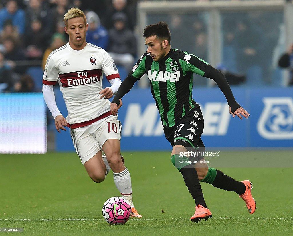 Keisuke Honda of AC Milan and Nicola Sansone of US Sassuolo Calcio in action during the Serie A match between US Sassuolo Calcio and AC Milan at Mapei Stadium - Città del Tricolore on March 6, 2016 in Reggio nell'Emilia, Italy.