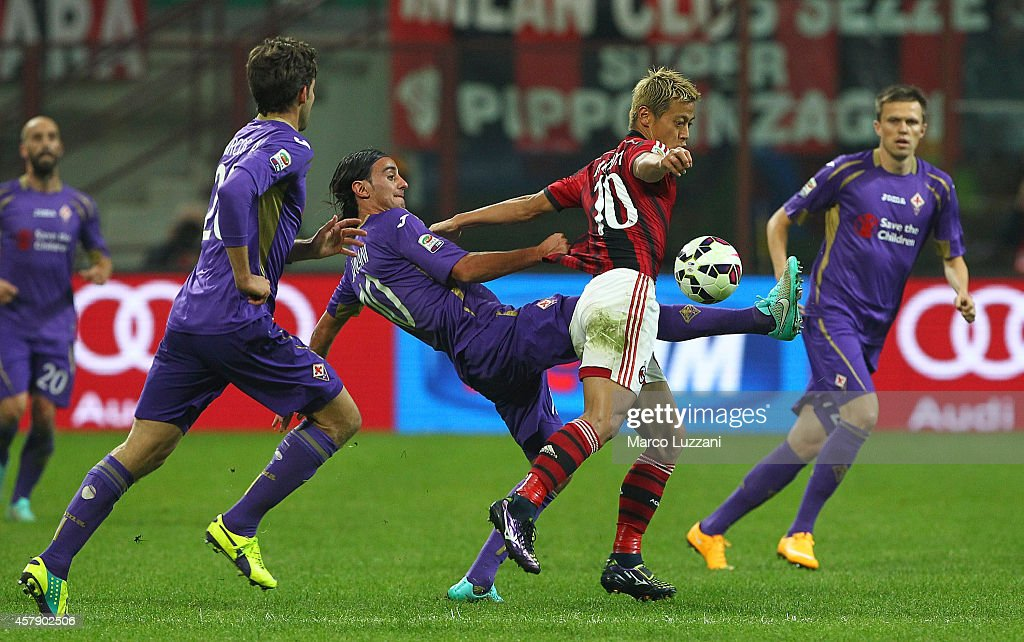 Keisuke Honda (R) of AC Milan competes for the ball with Alberto Aquilani (L) of ACF Fiorentina during the Serie A match between AC Milan and ACF Fiorentina at Stadio Giuseppe Meazza on October 26, 2014 in Milan, Italy.