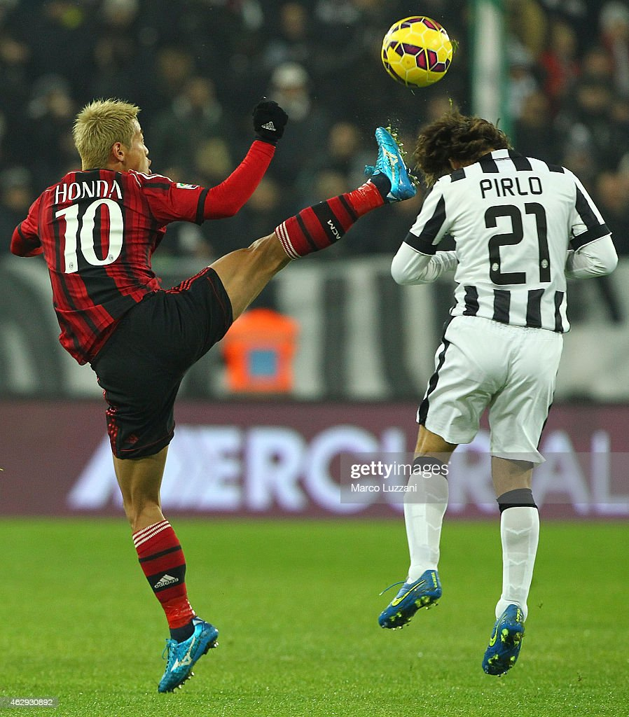 Keisuke Honda of AC Milan competes for the ball with Andrea Pirlo of Juventus FC during the Serie A match between Juventus FC and AC Milan at Juventus Arena on February 7, 2015 in Turin, Italy.