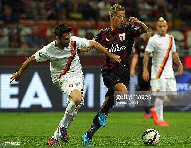 Keisuke Honda of AC Milan competes for the ball with Davide Astori of AS Roma during the Serie A match between AC Milan and AS Roma at Stadio...