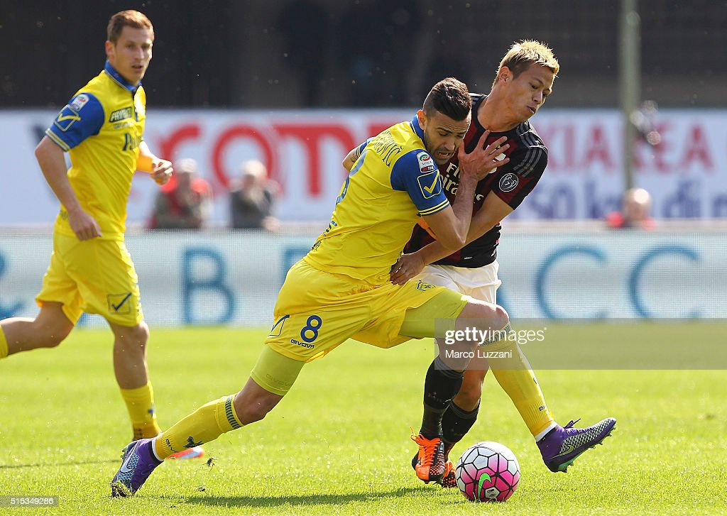 Keisuke Honda (R) of AC Milan competes for the ball with Ivan Radovanovic (L) of AC Chievo Verona during the Serie A match between AC Chievo Verona and AC Milan at Stadio Marc'Antonio Bentegodi on March 13, 2016 in Verona, Italy.