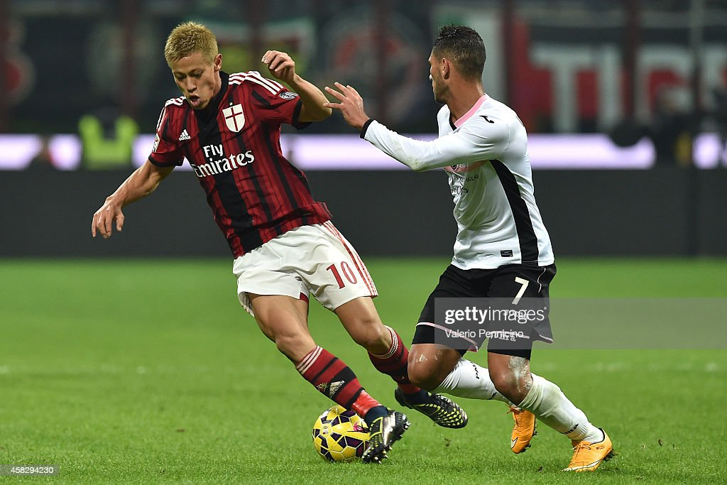 Keisuke Honda (L) of AC Milan is challenged by Achraf Lazaar of US Citta di Palermo during the Serie A match between AC Milan and US Citta di Palermo at Stadio Giuseppe Meazza on November 2, 2014 in Milan, Italy.