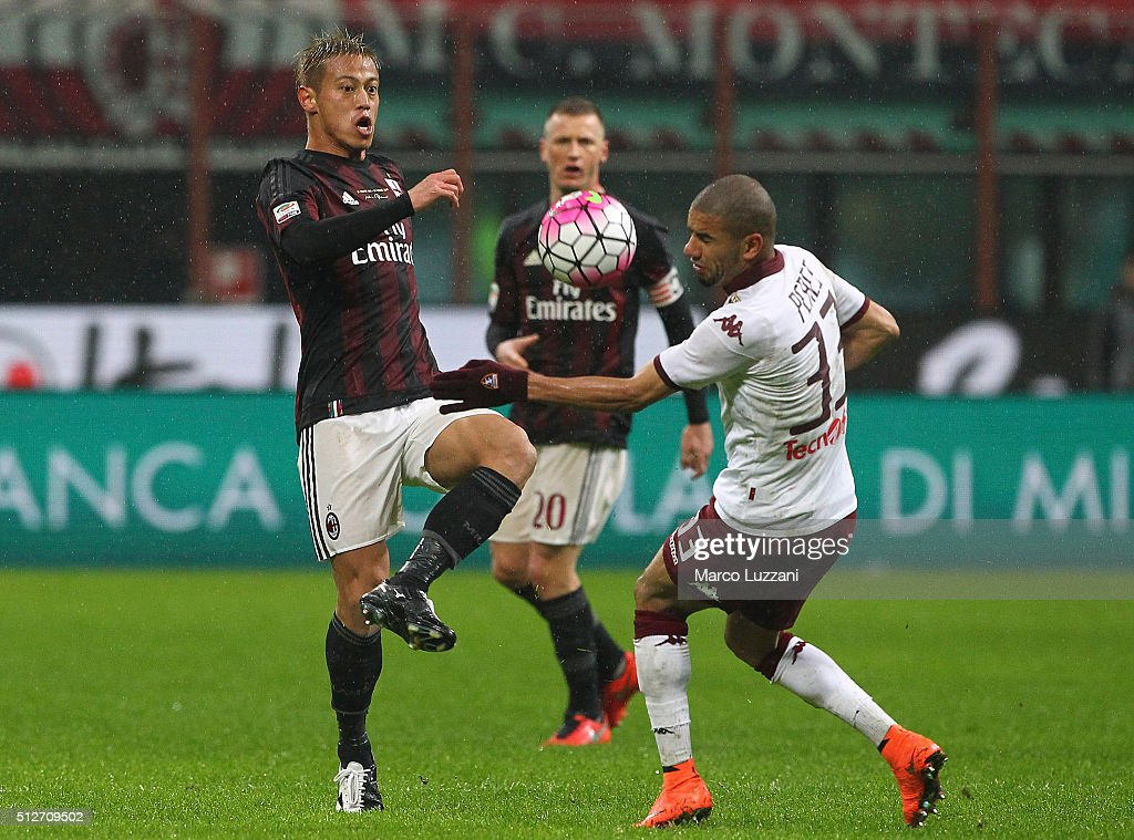 Keisuke Honda of AC Milan is challenged by Bruno Peres of Torino FC during the Serie A match between AC Milan and Torino FC at Stadio Giuseppe Meazza on February 27, 2016 in Milan, Italy.